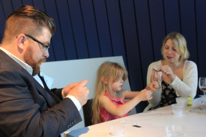 Chef Jonathon Sawyer, left, joins his 6-year-old daughter, Louisiana, and wife, Amelia, in stringing beads as part of the Community Chandelier Project at The Museum of Contemporary Art Cleveland. The chandelier is now an art installation at the Sawyers' new restaurant, Trentina.