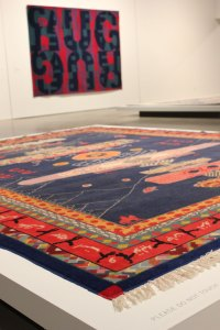 """An untitled work by Italian conceptual artist Alighiero e Boetti greets viewers to """"Wall to Wall."""" In the background is """"Carpet Rug"""" by Heimo Zobernig."""