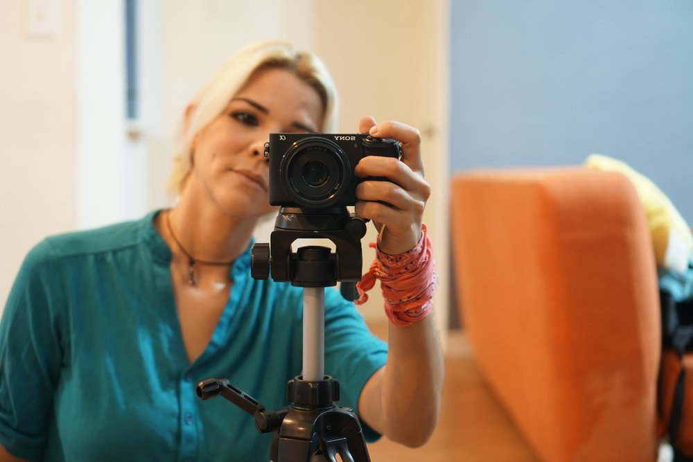 Photo of white blond woman behind camera on tripod by  Lilian Cordova  on  Unsplash