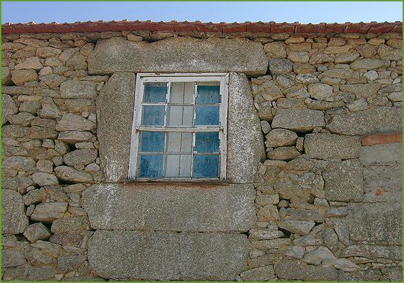 Janela de casa tradicional com as janelas de guilhotina e respetivas portas interiores