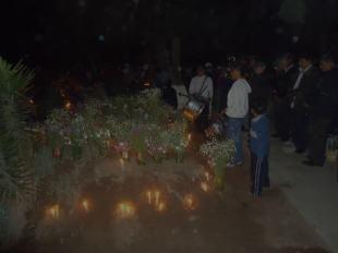 Rezos, flores, velas y música para nuestros muertos al pie de su tumba