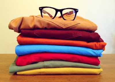 Clothes in several colors and glasses on top of a pile - just an example of what you can fit into any of our moving bins