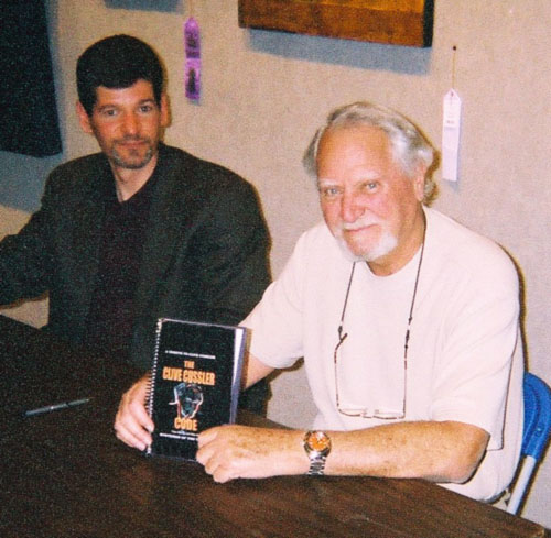 Dirk Cussler (left) making his dad happy by not talking; attempting to smile
