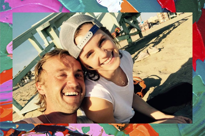 In the image actor Tom Felton is smiling leaning against Emma Watson's next door, also smiling. They're both on the beach.
