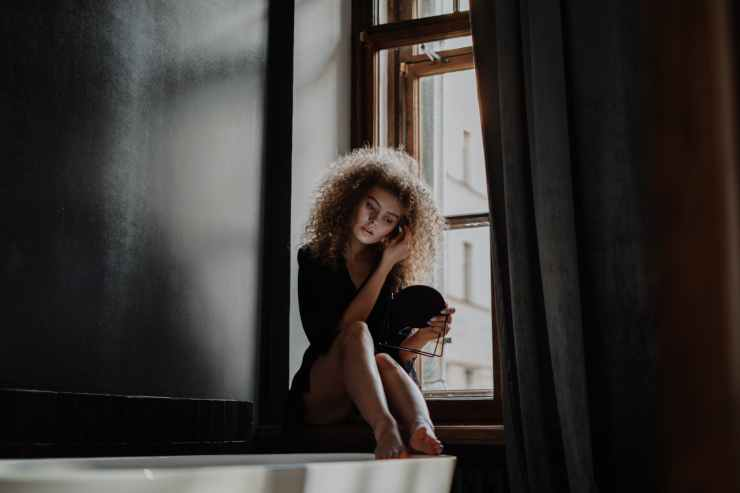 woman in black tank top sitting on window