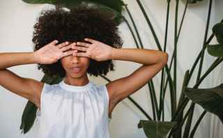 black woman covering face with hands standing near potted plant