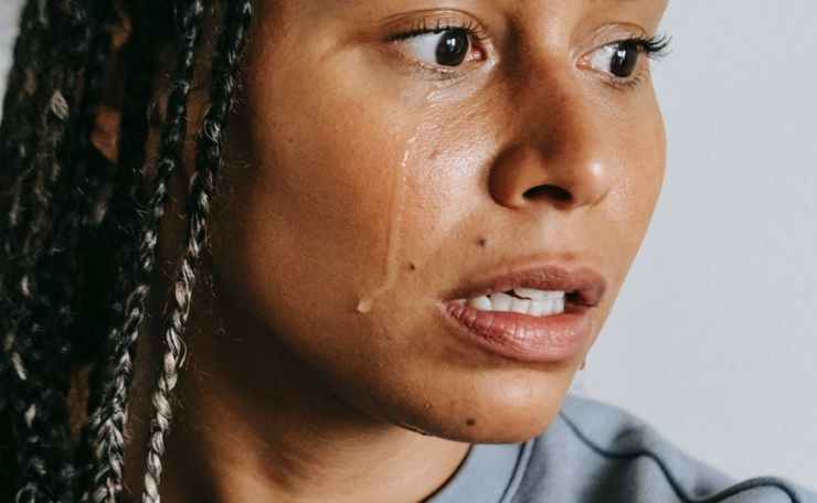 crying ethnic woman with afro braids on light background