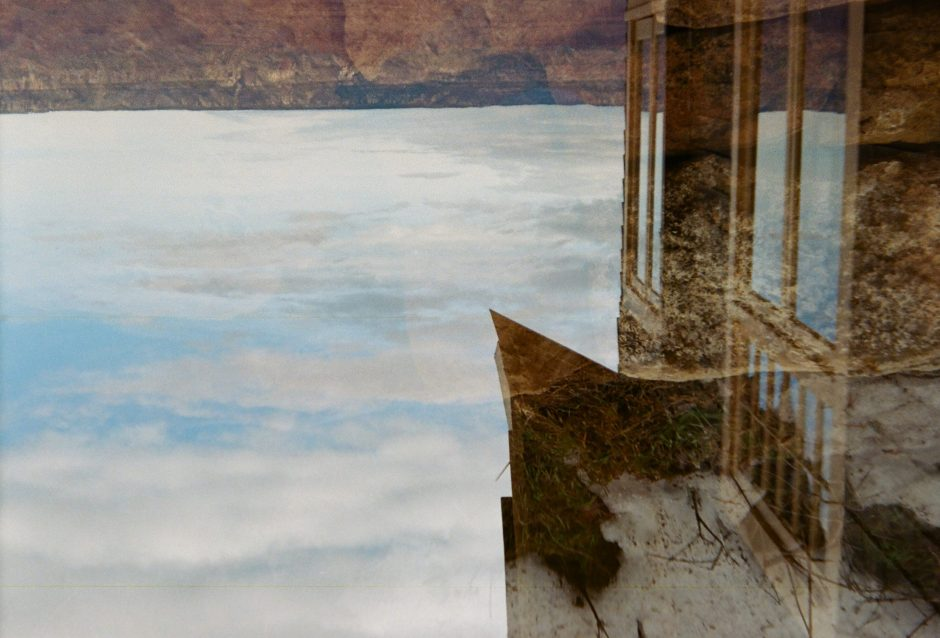 Double Exposure - grand canyon in the distance, house upside down in the foreground. Clouds scatter.