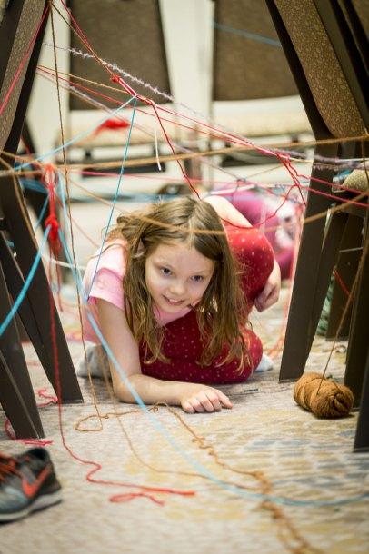 Child crawling through a yarn laser maze