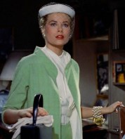 Grace Kelly as Lisa Fremont in Rear Window wearing a green suit and white pillbox hat.