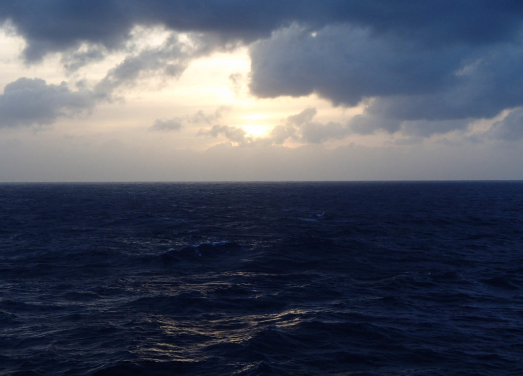 sun breaking out behind the clouds on a rough day at sea