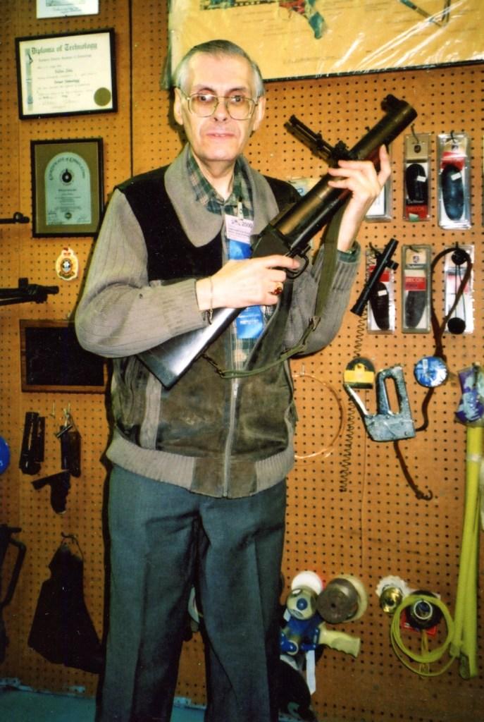 Man standing holding a grenade launcher.