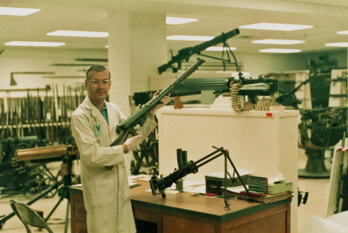 Barry Gillis at CWM arms vault 1985-08-29 - Holding Charlton automatic rifle conversion. Invented by a New Zealander, this appears to be an Australian made variant. An Italian Villa-Perosa sub-machine gun in on the desk. This was the World's FIRST SMG.