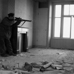 1945-04-07 Arthur Godin, a sniper with Le Regiment de la Chaudiere, Canadian Army at Zutphen, Netherlands. Notice that he is staying back in the room so that the enemy would have a difficult time spotting him. (L&AC MIKAN 3524681)