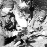 Corporal S. Kormendy and Sergeant H. A. Marshall cleaning their No. 4 MK. I (T) rifles.