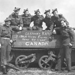 """Group of """"D"""" Company, Seaforth of C. personnel posing with Universal Carrier, 7 May 1945 in Holland. Another photo taken a few minutes before had VANCOUVER chalked on the side. This was rubbed out and CANADA chalked in to accommodate Seaforths who were not from Vancouver."""