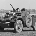 Ferret Scout Car with a helicopter hovering overhead.