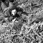 Canadian sniper making notes after observing during training in England.