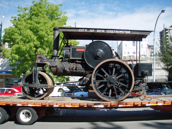 Road Roller on flat bed truck at a car show.
