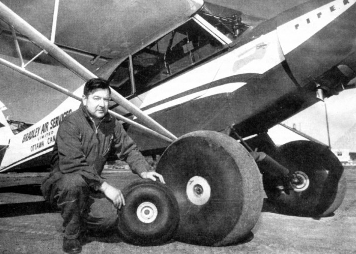 Man squatting beside small airplane with tires.