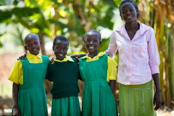 Sarah Wambrni Wamalwa standing with her two friends Ivy and Susan to her right and her teacher Metrine to her left