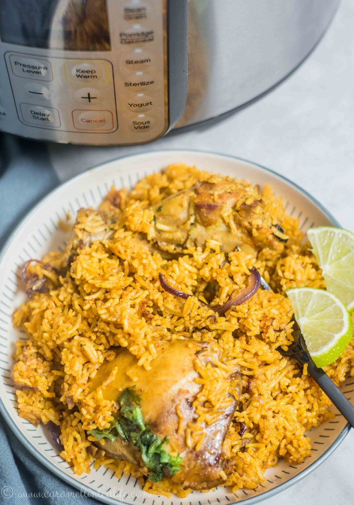 Chicken Biryani on a plate with lime wedges