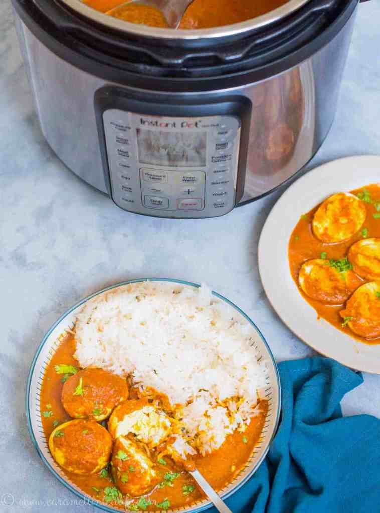 Instant Pot next to a plate of egg curry and rice