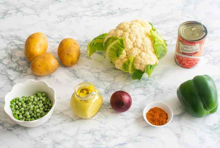 All ingredients needed to make pav bhaji on a white surface