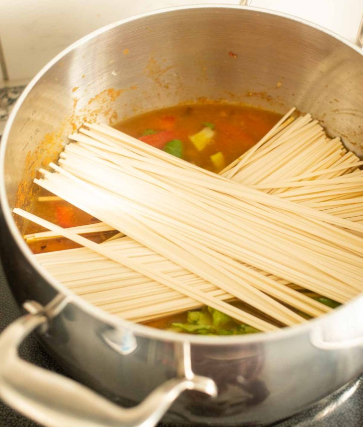 Raw udon noodles placed in a pot of soup on the stovetop