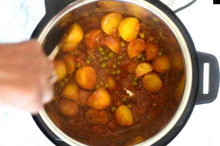 Ladle stirring potatoes and peas curry in an Instant Pot