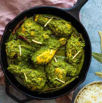saag chicken in a cast iron pan on a blue background