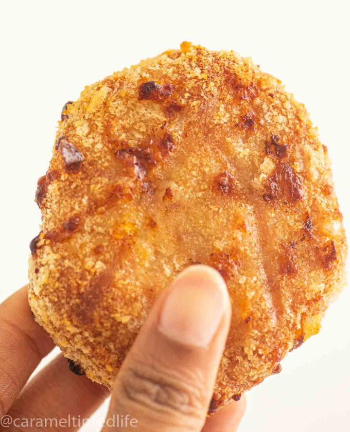 Fingers holding up a chicken patty