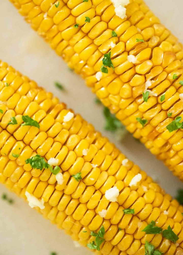 close up of corn on the cob with parsley and garlic