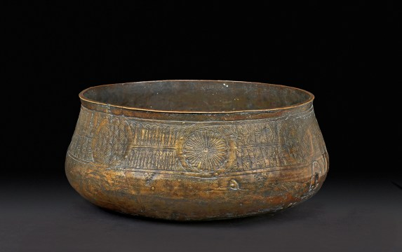 """Bowl (kuduo) Asante. Offin River, Ghana, mid–late 19th century. Brass. The British Museum, London, England, Af1955,05.225 This bowl was discovered in 1909 while dredging for gold along the banks of the Offin River in southern Ghana. Its formal similarity to the 14th- and 15th-century Mamluk brass bowls and basins manufactured thousands of miles away in Egypt provides compelling evidence that it was inspired by the northeastern African imports. Its profile and surface decoration are almost identical to Mamluk period Arabic-inscribed bowls, but details such as the use of """"pseudo script""""— an attempt by an artist unfamiliar with Arabic to capture the formal essence of Arabic calligraphy— and the representation of stylized crocodiles and mudfish, inhabitants of the Akan forest, in two of the eight medallions reveal that it is of local manufacture."""