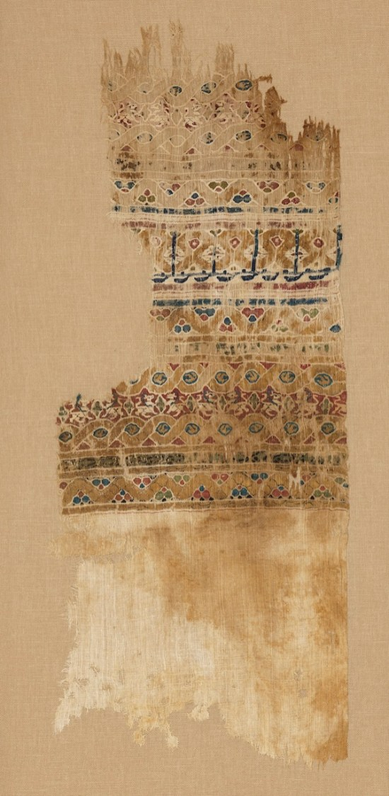 """Tiraz textile fragment. Egypt, 12th century. Linen and silk. Royal Ontario Museum, Toronto, Canada, Abemayor Collection given in memory of Dr. Veronika Gervers, Associate Curator, Textile Department (1968-1979) by Albert and Federico Friedberg, 978.76.504.A. Extremely fine silk and linen tiraz textiles, occasionally embellished with gold-wrapped silk threads, were produced in private and state-run factories during the Fatimid and Mamluk periods, from the 10th to the 14th century. Many tiraz textiles bear inscriptions recording the names, titles, and dates of rulers, as well as declarations of faith. The """"robes of honor"""" reportedly given to Mansa Musa were almost certainly tiraz, as they were among the high-value gifts presented to visiting dignitaries by rulers."""