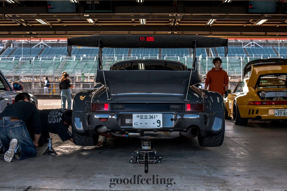 RWB Porsche 930 in grey with the rear jacked up, shown from the rear in a garage at Twin Ring Motegi Circuit, Japan