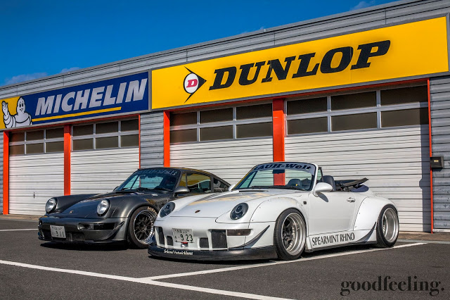 "RWB Porsche convertible nicknamed ""Spearmint Rhino"" in white with the top down, next to a grey RWB Porsche at a racetrack in Japan"