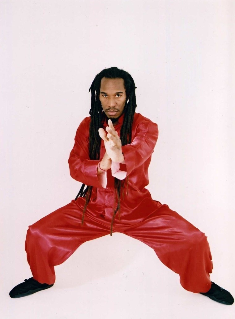 Benjamin Zephaniah in a karate pose in a red outfit, looking into the camera.