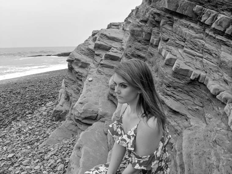 Mari Ellis Dunning sitting on a beach, looking away from the camera.