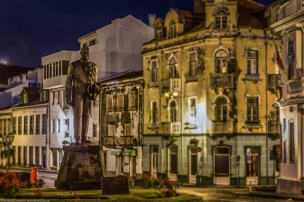 Version 2 of Night photography of a statue in the rainy streets of Horta.