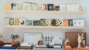 various literature on wooden shelves in modern bookstore