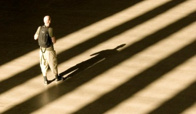 Man standing and facing very large shadows.