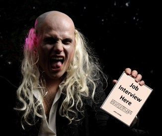 "A scary-looking character from ""Rocky Horror Picture Show"" holding a handbill which reads ""Job Interview Here."""