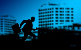 Silhouette of a person, in a city, running with a briefcase.