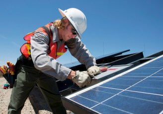 Man in hardhat with tool belt working on solar panel.