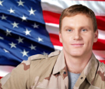 Man in fatigues smiling in front of American flag background
