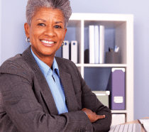 An older African-American woman sitting at a desk with arms crossed, smiling