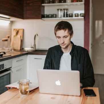 thoughtful male student working on laptop in kitchen at home
