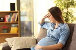worried pregnant woman on couch