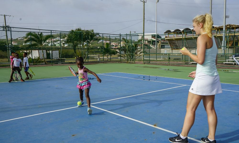 A volunteer running a tennis coaching session in St Lucia